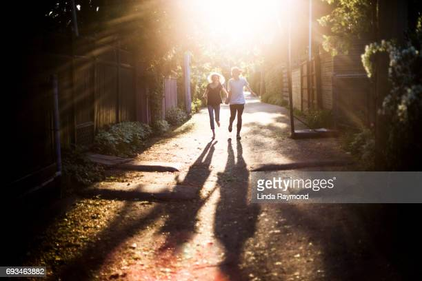 A young couple running hand in hand in an alley at sunset