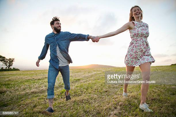 Young couple running hand in hand in rural field, Dorset, England