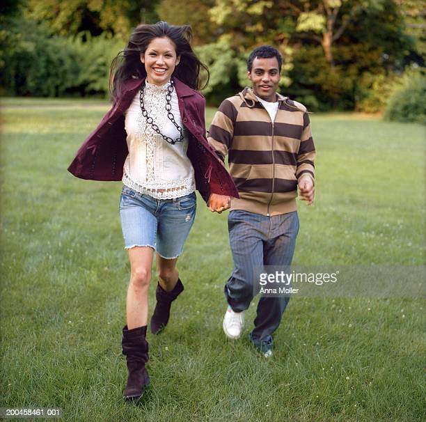 Young couple running in park, holding hands