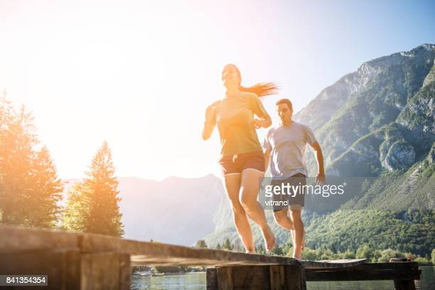 Young couple running on pier by lake