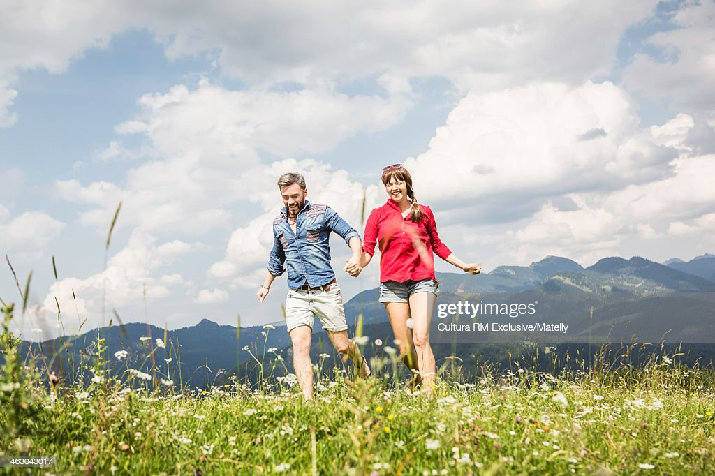 young couple running through grass tyrol austria stock. Black Bedroom Furniture Sets. Home Design Ideas