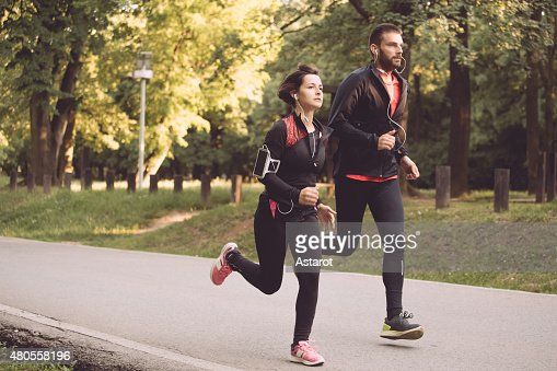 Young couple running together in park : Stock Photo