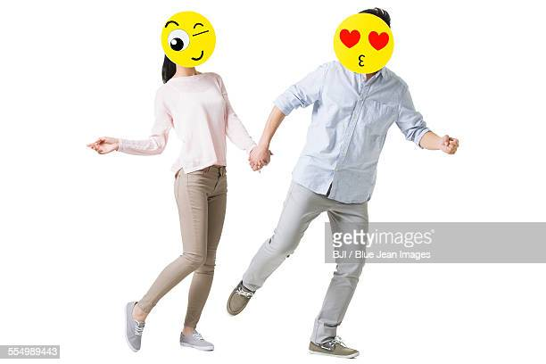 Young couple running with cartoon emoticon faces in front of their faces