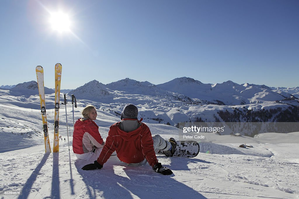 Young Couple Sat On Ski Slope Stock Photo