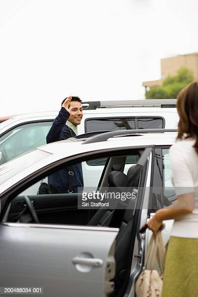 Young couple saying goodbye to each other in parking lot