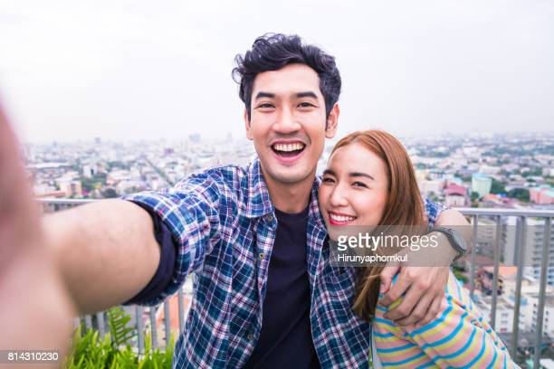 POV young couple selfie big smile at rooftop