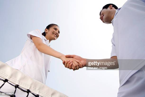 Young couple shake hands on the tennis court