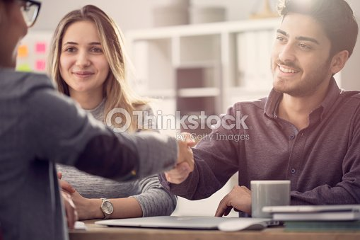 Young couple shaking hands with a female agent : Stock Photo