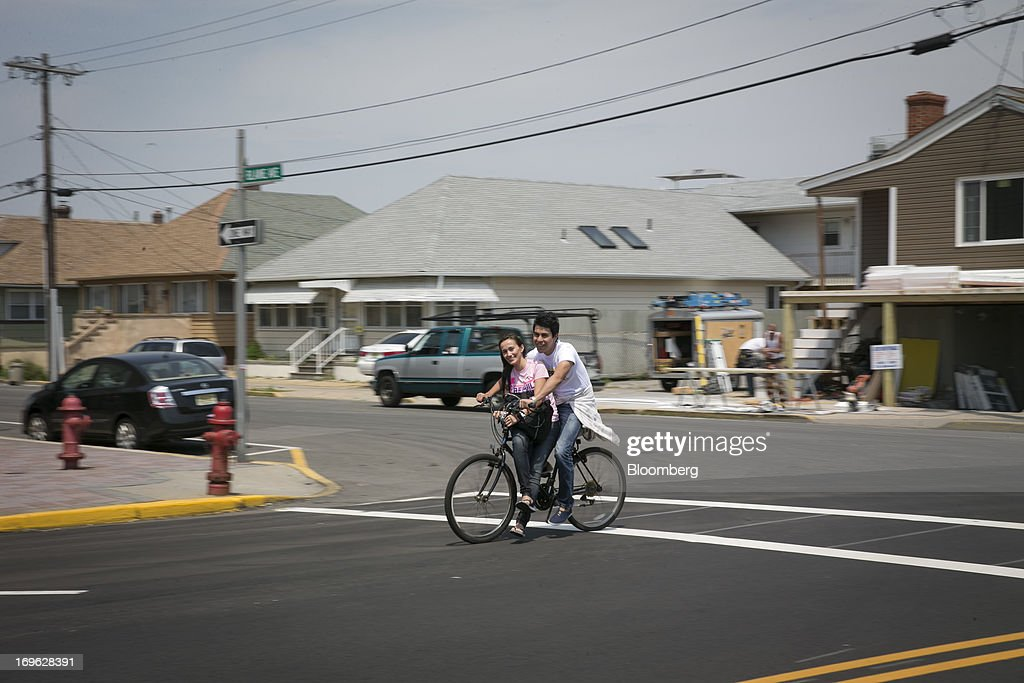 A young couple shares a ride on a bicycle in Seaside Heights, New Jersey, U.S., on Wednesday, May 29, 2013. Sandy, which came ashore near Atlantic City, killed dozens of people and destroyed more than 365,000 homes in the state. Christie has said it will cost $36.9 billion for repairs and to prevent devastation from future storms. Photographer: Scott Eells/Bloomberg via Getty Images
