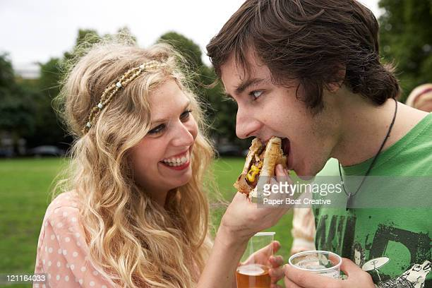 Young couple sharing a burger in the park
