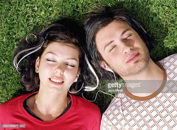 Young couple sharing earphones lying on grass, close-up