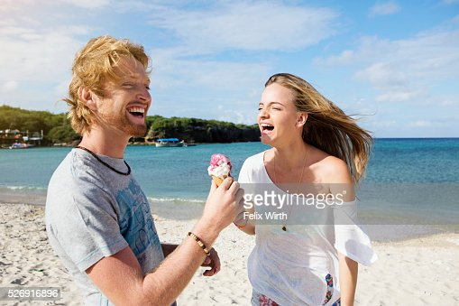 Young couple sharing ice cream at beach : Stock-Foto