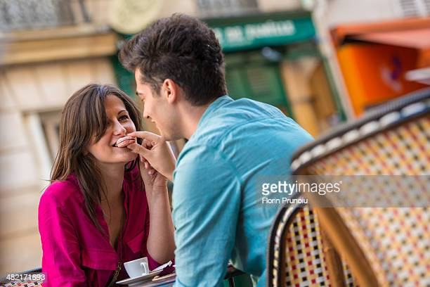 Young couple sharing macaroon at pavement cafe, Paris, France