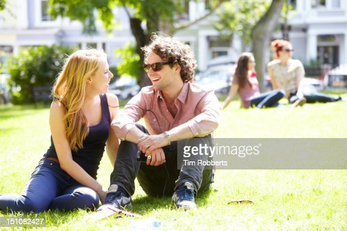 Young couple sharing music in urban park : Stock Photo