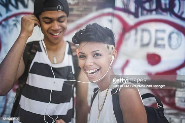 Young couple sharing music on earphones