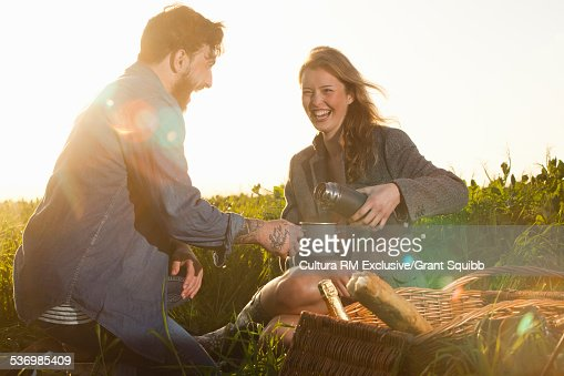 Young couple sharing picnic in rural field