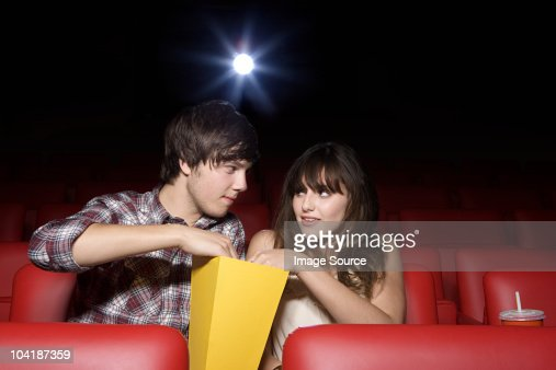 Young couple sharing popcorn in movie theater : Stock Photo