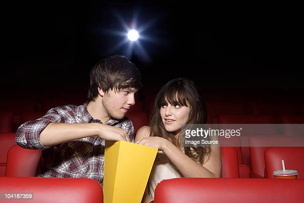 Young couple sharing popcorn in movie theater