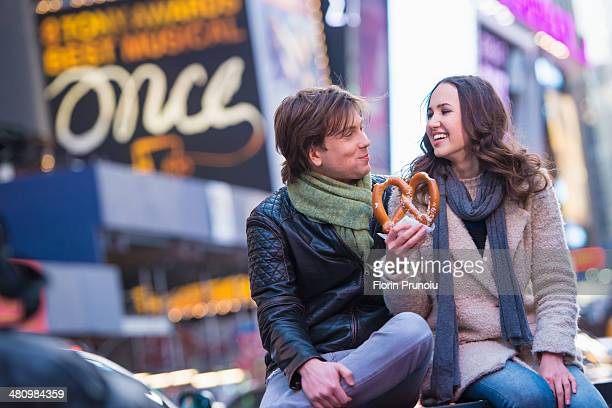 Young couple sharing pretzel, New York City, USA