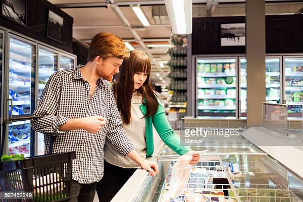 Young couple shopping at freezer section in supermarket
