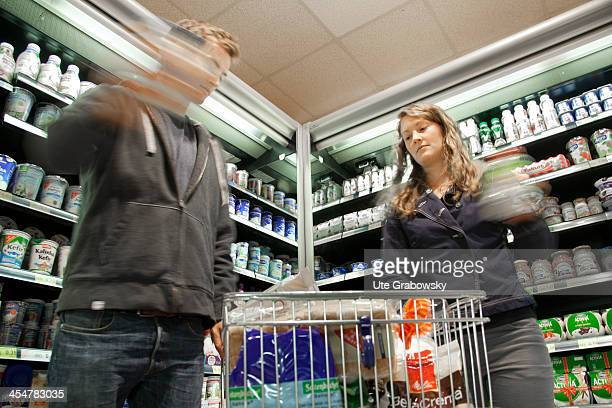 A young couple shopping in the refrigerated section of a supermarket pictured on July 04 2013 in Bonn Germany