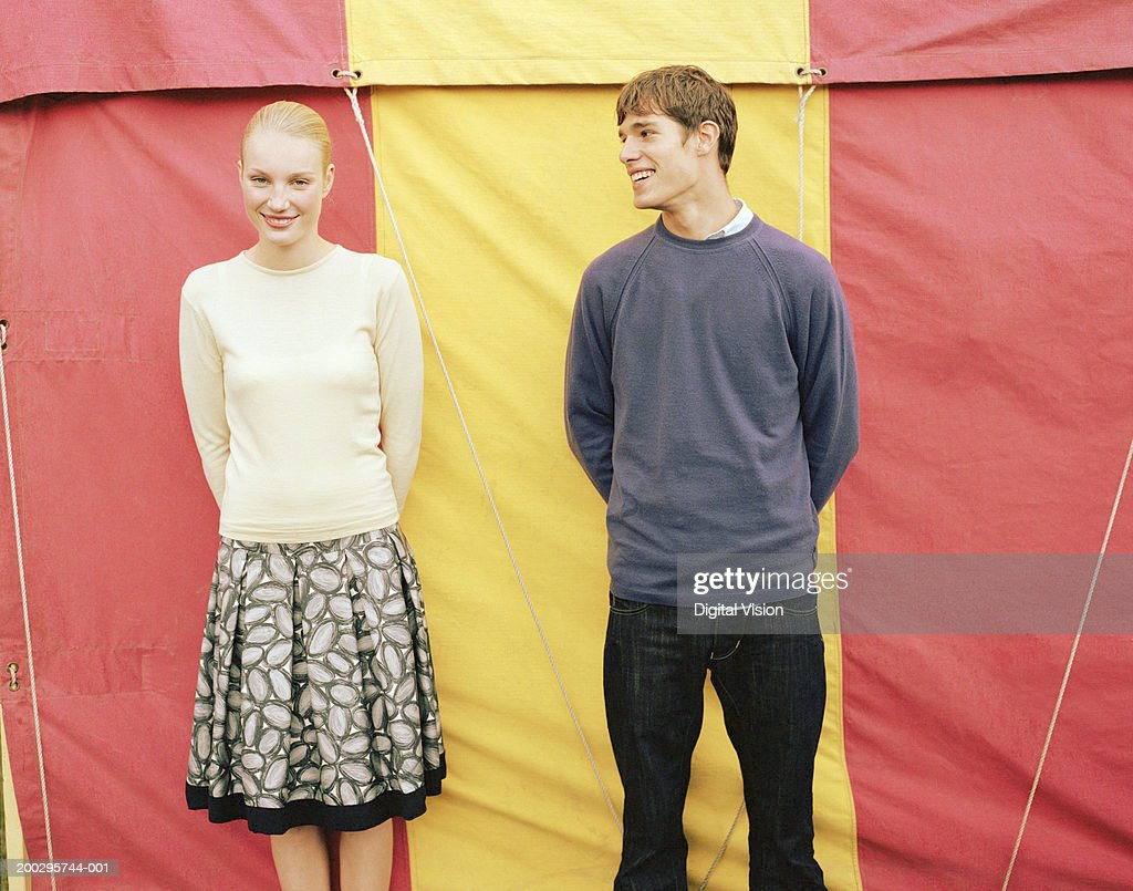 Young couple side by side in front of fairground tent, portrait of woman : ストックフォト