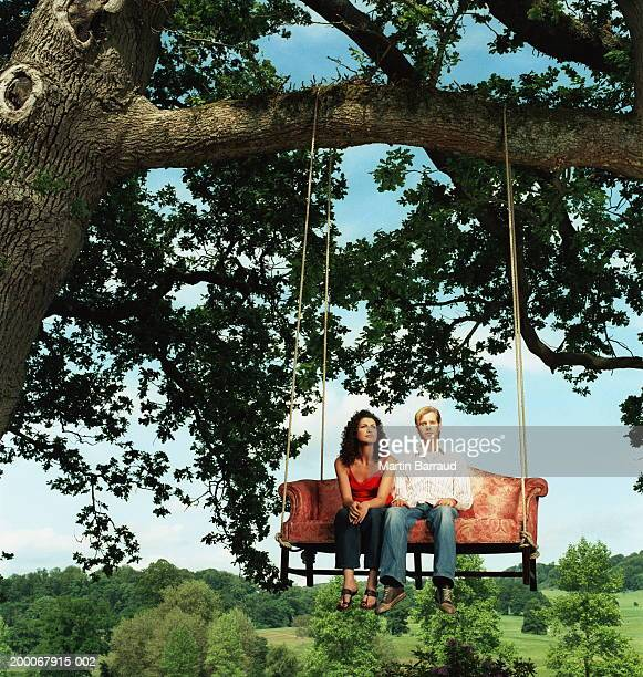 Young couple side by side on sofa strung from tree, portrait of man