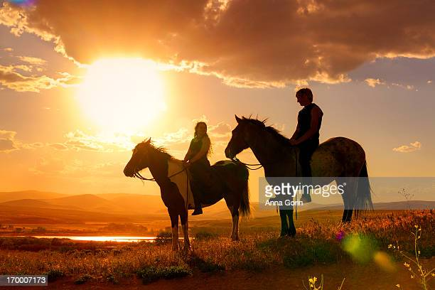 Young couple silhouetted on horseback at sunset