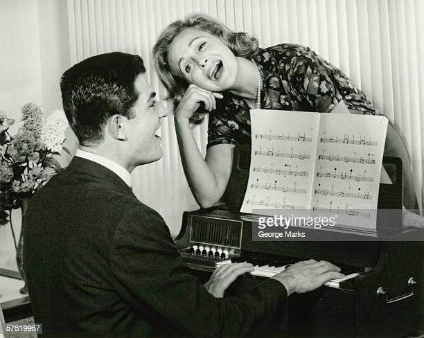Junges Paar singen, man spielt Klavier, (B & W