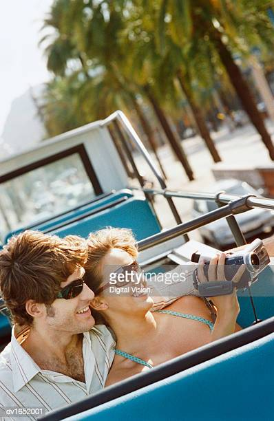 Young Couple Sit Side by Side on an Open Top Bus, Filming With a Camcorder