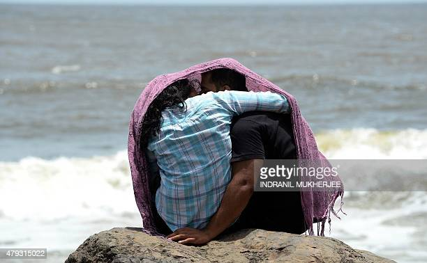 A young couple sit together on a rocky outcrop off the Arabian sea in Mumbai on July 3 2015 AFP PHOTO / INDRANIL MUKHERJEE