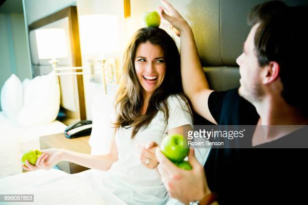 A Young Couple Sits In A Dallas Hotel Room Side By Side and Plays With Apples