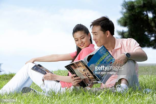 A young couple sits on the grass reading a magazine.