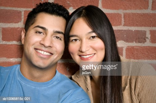 Young couple sitting against brick wall, smiling, close-up, portrait