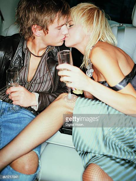 Young Couple Sitting and Kissing in the Back Seat of a Limousine With Champagne