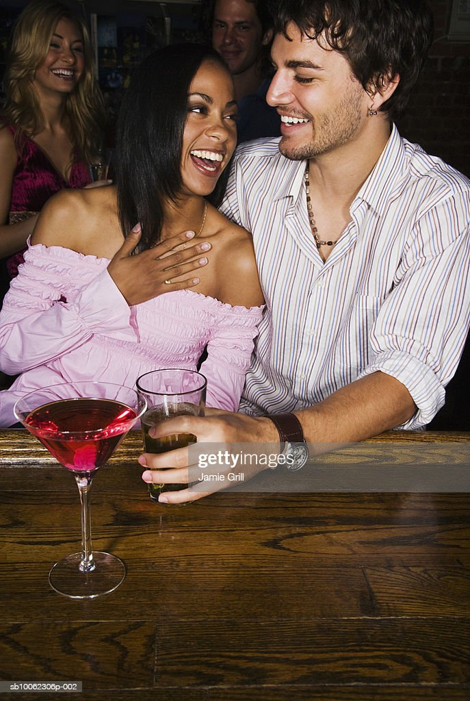 Young couple sitting at bar area, laughing : Stock Photo