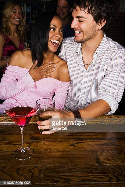 Young couple sitting at bar area, laughing