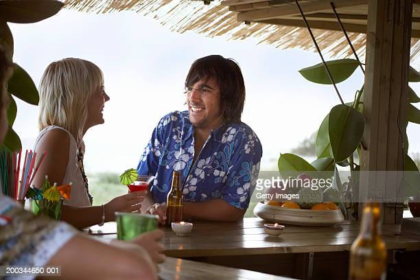 Young couple sitting at beach bar, smiling at each other