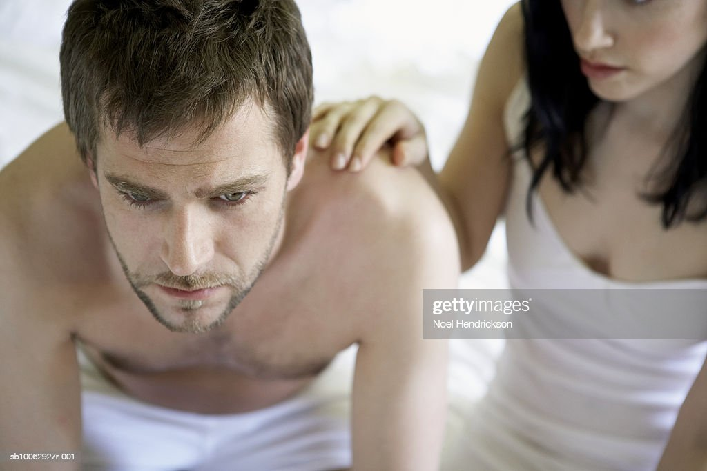 Young couple sitting at edge of bed, man worried, high angle view : Stock Photo