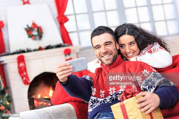 Young couple sitting at home and making selfie with presents