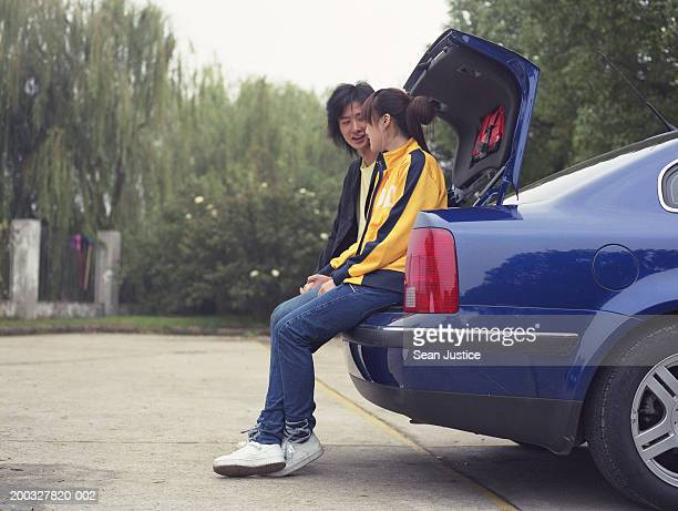 Young couple sitting at rear of car, talking, side view