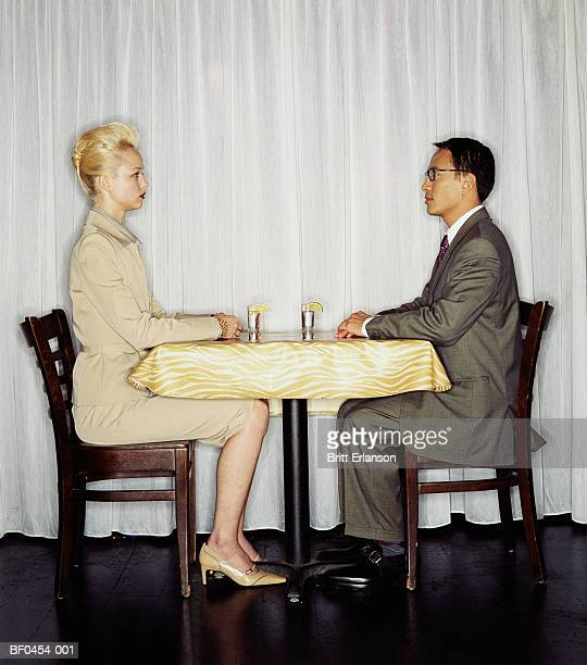 Young couple sitting at table, face to face