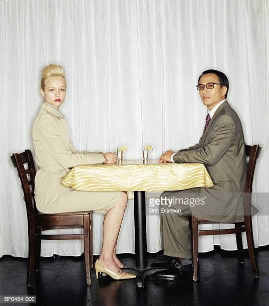 Young couple sitting at table, portrait