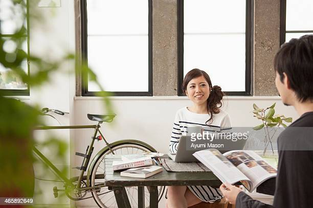 Young couple sitting at table with computer