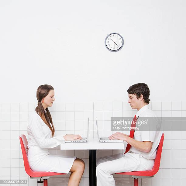 Young couple sitting at table, working on laptops, side view