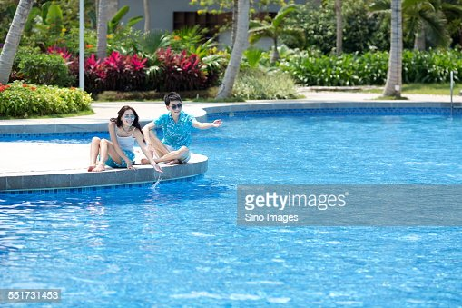 Young Couple Sitting by a Swimming Pool