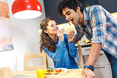 Young couple sitting by table and eating breakfast early in the morning together.