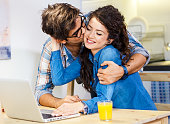 Young couple sitting by table with laptop and eating breakfast early in the morning together.