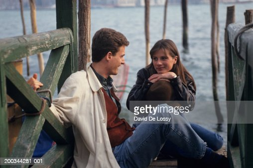 Young couple sitting by waterfront, talking : Stock Photo