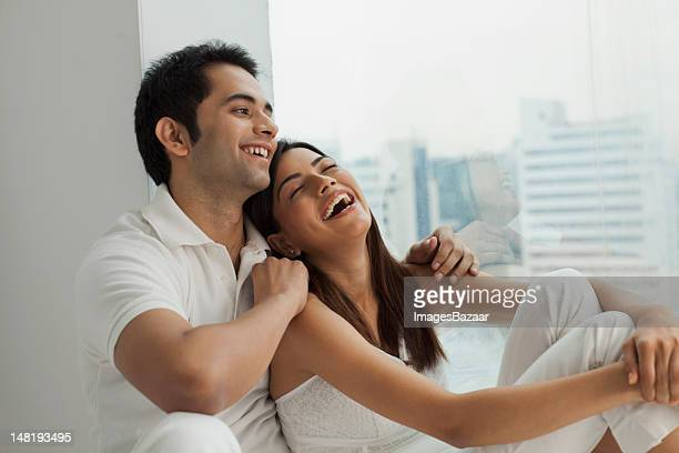 Young couple sitting by window and laughing